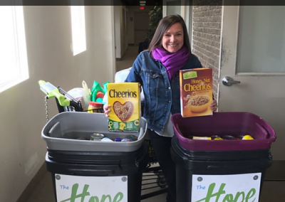 woman donating cereal in bins