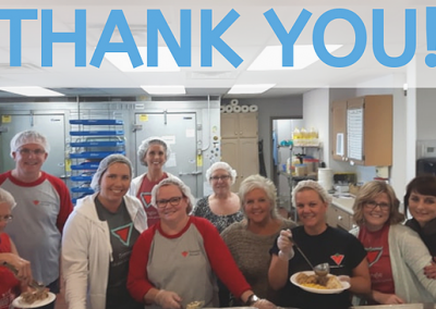 volunteers in the kitchen with a thank you sign
