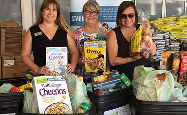 three women stand behind donated goods
