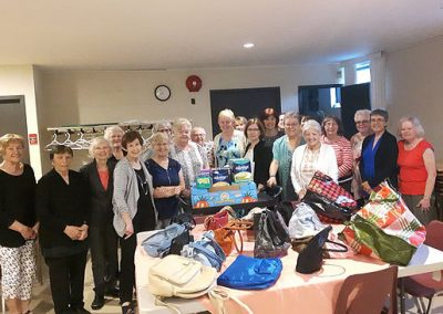 volunteers stand around donation and collection of purses and bags on a table in front