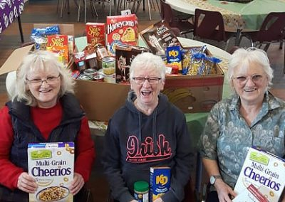 three women in front of gathered food donations
